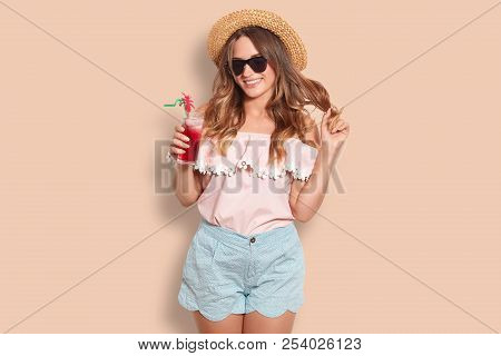 Beautiful Cheerful Female Rests In Resort Country, Holds Summer Fresh Cocktail, Wears Trendy Sunglas