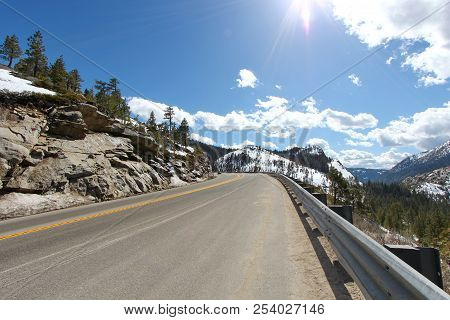 A Road To Lake Tahoe With Snow Capped Mountains.