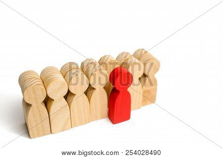 The Chosen Person Among Others. A Human Figure Of Green Color Stands Out From The Crowd. Wooden Figu
