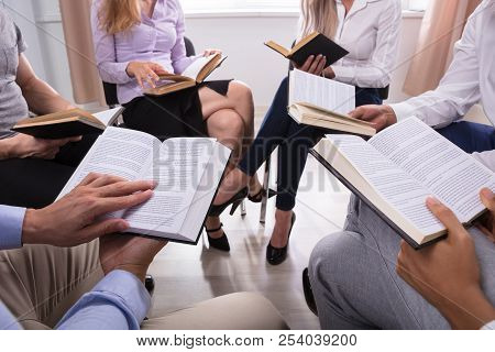 Group Of People Sitting In A Circle Reading Holy Books