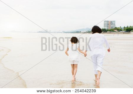 Happy Asian Family Mother And Child Daughter Run, Laugh And Play At Beach. Happy Family Summer Vacat
