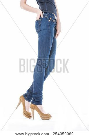 Fashion. Woman legs in jeans and high heels shoes posing