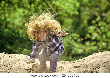 Boy Jump On Pile Of Sand On Idyllic Day. Child Play In Sand In Spring Or Summer Park. Childhood, Pla