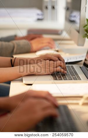 Hands Of Software Developers Working On Computers At Table In Office