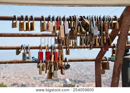 BARCELONA, SPAIN - APRIL 18, 2018: Padlocks placed as symbols of love and friendship on the railings at the summit of Mount Tibidabo. The custom is seen in numerous places around the World.