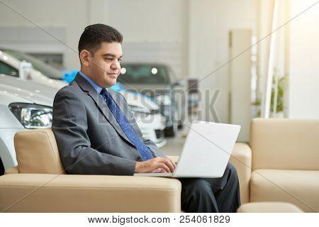 Businessman Working On Laptop In Car Dealership
