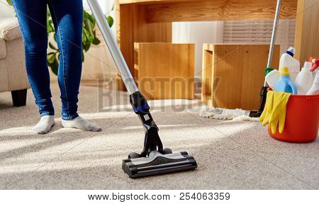 Close Up Of Young Woman In Jeans Cleaning Carpet With Vacuum Cleaner In Living Room, Copy Space. Hou