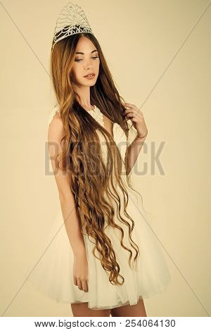 Haircare and prom queen. Beauty salon and wedding fashion. Woman with long hair white dress and crown. Hairdresser and cosmetics. Girl has fashionable makeup and healthy hair on grey background. poster