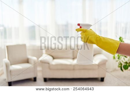 Woman's Hand In Yellow Protective Glove Holding White Spray Bottle With Living Room In Blur On Backg