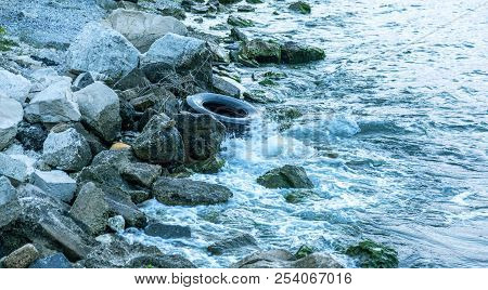 Used Car Tires Remained In Nature. The Old Unnecessary Tire Of Car Remained In The Water. The Proble