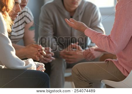 Close-up Of A Therapist Gesticulating While Talking To A Group Of Listing Teenagers During An Educat