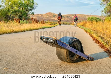 Windsor, CO, USA - August 15, 2018:  Onewheel electric skateboard and cyclists in the late summer morning on the Poudre River Trail in northern Colorado.