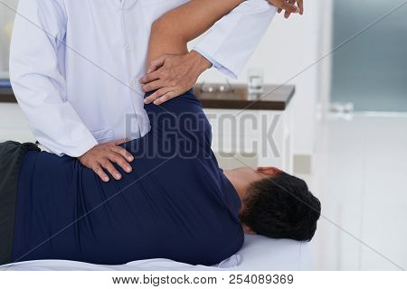 Chiropractor Adjusting Spine Of Patient With Back Pain