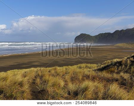 Brown Sand Windy Beach. Blue Sky With Clouds. Steep Mountain Rising From The Water. Green Dune. Land