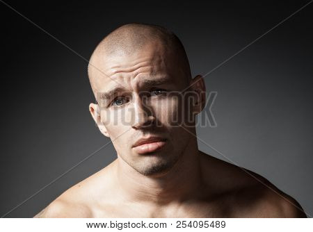Portrait Of Pitiful Strong Man Isolated On Gray Background