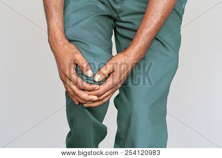 Pain In Knee. Close-up African Male Leg With Painful Kneeson On Gray Background. Man Feeling Joint P