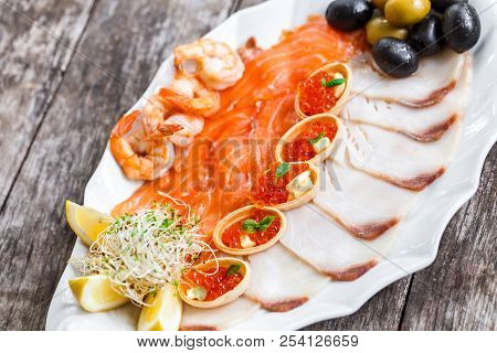 Seafood Platter With Salmon Slice, Pangasius Fish, Red Caviar, Shrimp, Decorated With Olives And Lem