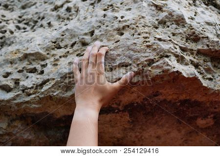 Photo Of Man's Hand Clambering Over Rock