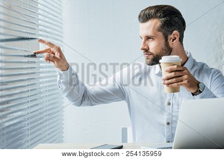 Businessman Holding Coffee To Go And Looking At Window Through Jalousie