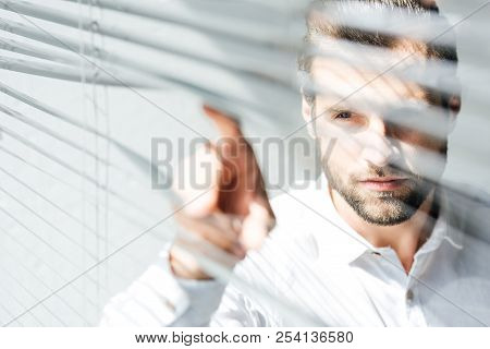 Serious Man Looking Through Window Jalousie, Selective Focus