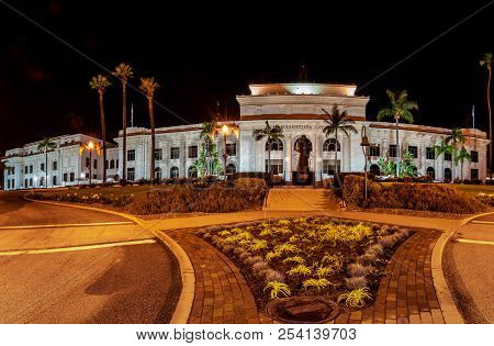 Panoramic View Of Ventura City Hall Building Lit Up At Night With Landscaping And Junipero Serra Sta