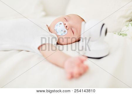 Baby with pacifier in mouth sleeps peacefully with baby monitor on cot