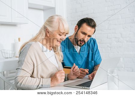 Smiling Senior Woman Holding Credit Card And Using Laptop With Young Caregiver