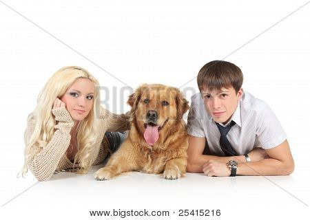 A Young Family With A Dog On Floor, Looking At Camera
