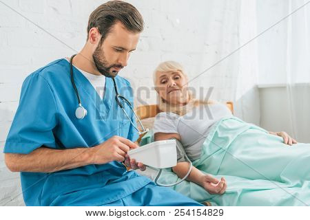 Young Male Nurse With Stethoscope Holding Blood Pressure Monitor While Measuring Blood Pressure To S