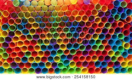 Hundreds Of Colorful Plastic Straws Laying Facing Forwards Opening Towards Viewer, Laying On Yellow