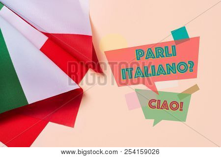 some flags of Italy and the question parli italiano? do you speak Italian? written in Italian, on a pink background