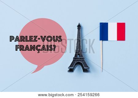 a miniature of the Eiffel Tower, a flag of France and the question parlez-vous francaise, do you speak French? written in French, against an off-white background