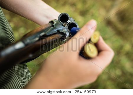 Autumn hunting season. Hunting. Outdoor sports. Woman hunter in the woods - detail of the rifle being loaded