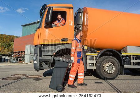 Two garbagemen working together on emptying dustbins for trash removal