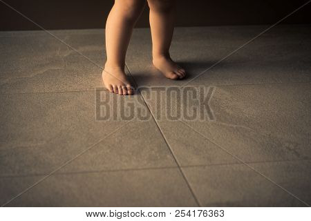 Barefoot Baby Are Staying On Heating Tile Floor.