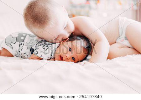 Elder Brother Blonde Hair Kiss Baby Sister Lying On Bed