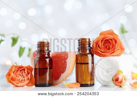 Essential Oil Bottles With Towel, Grapefruit And Rose Flowers On White Table. Spa, Aromatherapy, Wel