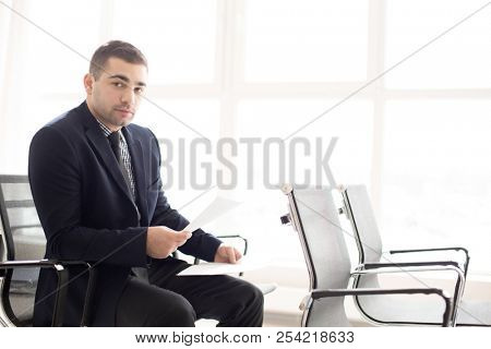 Adult handsome man in suit sitting on chair in conference hall holding papers and looking at camera