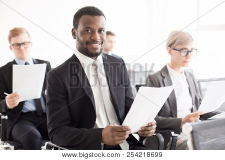 Cheerful African-American man in suit sitting with coworkers in conference hall smiling at camera having business meeting