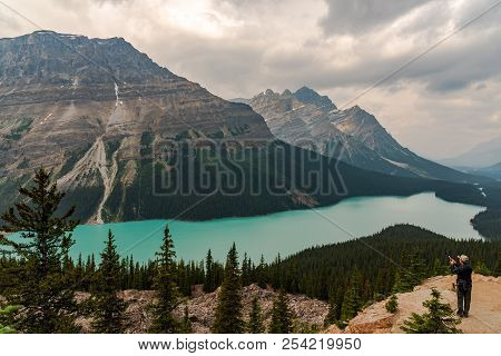 Banff, Canada -- August 3, 2018. Man With A Selfie Stick Takes A Photo While Overlooking Peyto Lake.