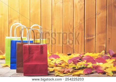 Autumn Shopping. Color Paper Bags For Shopping On Fallen Leaves Over Wooden Background. Copy Space.