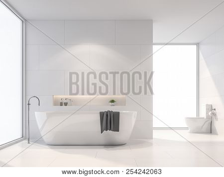 Modern White Bathroom 3d Render. There Are White Tile Wall And Floor.the Room Has Large Windows.sunl