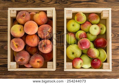 Small Wooden Crates Of Healthy Fresh Fruit Filled With Ripe Peaches And Variegated Apples View From