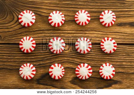 Neat Rows Of Popular Mint Flavored Boiled Red And White Starlight Candies Over A Rustic Wooden Backg