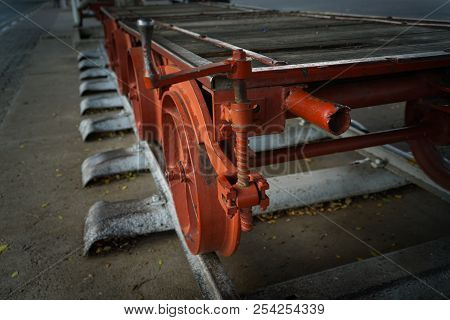 Old-fashioned obsolete railway rolling stock close-up for freight transport with winding mechanism for lifting freight tray, poster