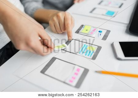 app design, technology and business concept - web designers or developers working on user interface wireframe layout at office