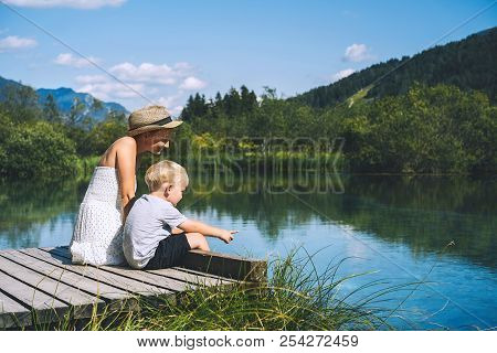 Mother And Son On Wooden Bridge On Nature Background Of Lake And Mountains. Travel, Family, Lifestyl