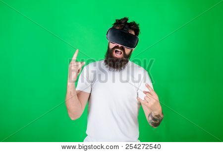 Man With Beard In Vr Glasses, Green Background. Hipster On Shouting Face Shows Sign Of Horns While I