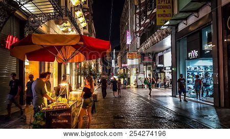 Athens, Greece - September 12 2016: A Young Woman Waits For Her Food At A Food Cart On A Rainy Night