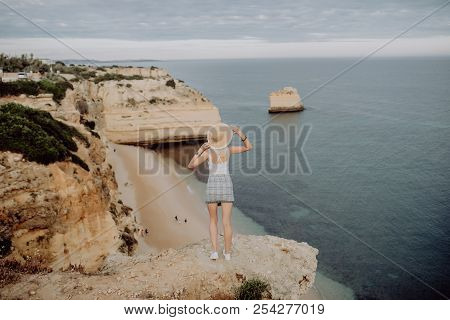 Young Beauty Woman In Straw Hat Enjoying Great View On The Rocky Coastline During The Sunrise In Lag